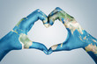 canvas print picture - Female hands, painted in the world map,  forming heart shape isolated on blue background