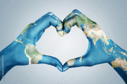 Female hands, painted in the world map,  forming heart shape isolated on blue background #330497255