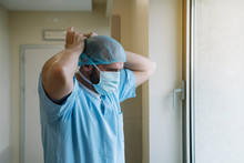 Staff Putting On Mask In Hospital
