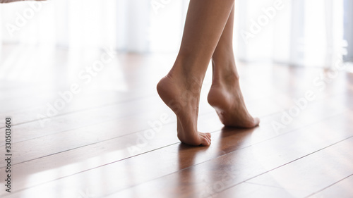 Fototapeta Close up focus on young female feet walking barefoot on clean wooden floor at home. Cropped image millennial woman girl standing on warm floor without slippers indoors, underfloor heating concept. obraz