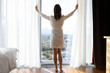 Full length back rear view young slim brunette woman in nightgown bathrobe standing barefoot near big panoramic window, opening curtains, enjoying good morning vacation time alone at home hotel.