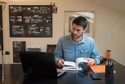 Fotografiet Young male studying for university at home via online lessons during the coronavirus quarantine
