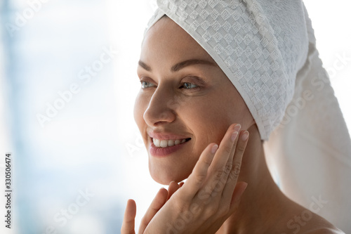 mata magnetyczna Close up head shot beautiful happy young woman with towel on head looking away in mirror, touching facial skin. Smiling attractive lady doing morning skincare routine in bathroom after showering.