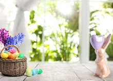 Bright Easter Eggs In Wicker Basket And Bunny Figure On Table Indoors