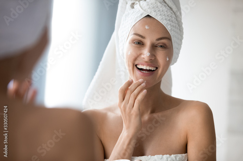 Obraz na plátně Attractive young lady with towel on head applying moisturizing smoothing cream on face after showering, excited by good cosmetics results