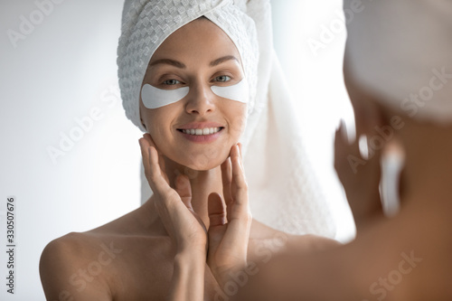 Fototapeta Mirror reflection attractive 30s lady with eye area care patches, head shot close up. Smiling pretty woman reducing facial wrinkles, moisturizing skin under eyes, looking at camera. skincare routine. obraz na płótnie