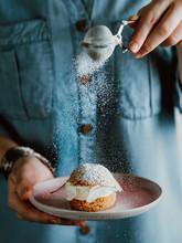 Woman Sprinkles Icing Sugar On...