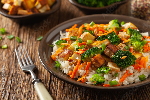 Fototapeta Tofu with rice and vegetables. Served on brown plate. obraz
