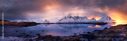 Fototapeta A stunning panoramic sunrise shot of a colorful winter scene with mountains in