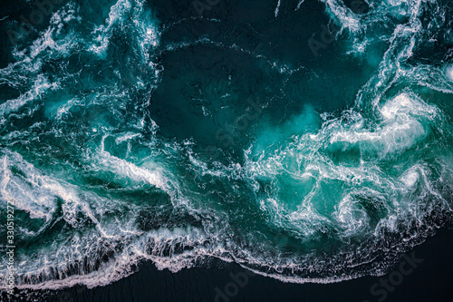 Carta da parati Waves of water of the river and the sea meet each other during high tide and low