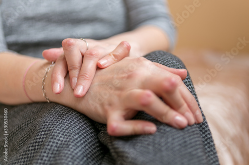 Young woman having rheumatoid arthritis takes a rest sittinng on the couch Wallpaper Mural