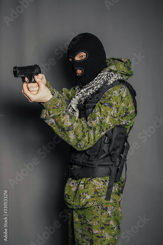 Fotografia, Obraz A man in camouflage uniform, body armor and a balaclava, holds his weapon ready and takes aim with a pistol, standing against a gray background