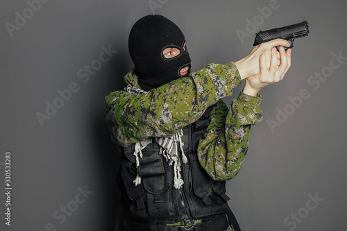 A man in camouflage uniform, body armor and a balaclava, holds his weapon ready and takes aim with a pistol, standing against a gray background Tablou Canvas