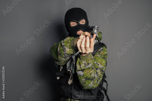A man in camouflage uniform, body armor and a balaclava, holds his weapon ready and takes aim with a pistol, standing against a gray background Fototapet