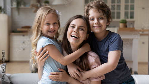 Fototapeta Close up portrait of excited young mother and little preschooler children hug cuddle look at camera laughing and posing together, overjoyed mom or nanny relax play with small kids at home obraz