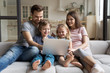 Overjoyed young family with small children sit relax on comfortable couch at home enjoying funny video on laptop, happy parents rest with kids on cozy sofa watching movie using computer together