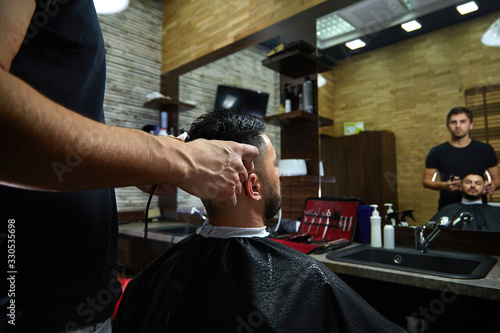 Fotografiet a brutal-looking Barber cuts the hair of an Indian guy