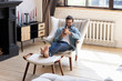 Leinwandbild Motiv Smiling young man using smartphone, sitting in armchair in modern living room, happy male holding phone, looking at screen, chatting in social network or shopping online, playing game, using apps