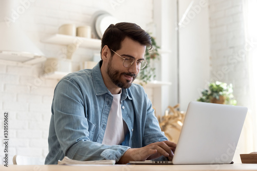 Obraz Focused young man wearing glasses using laptop, typing on keyboard, writing email or message, chatting, shopping, successful freelancer working online on computer, sitting in modern kitchen - fototapety do salonu