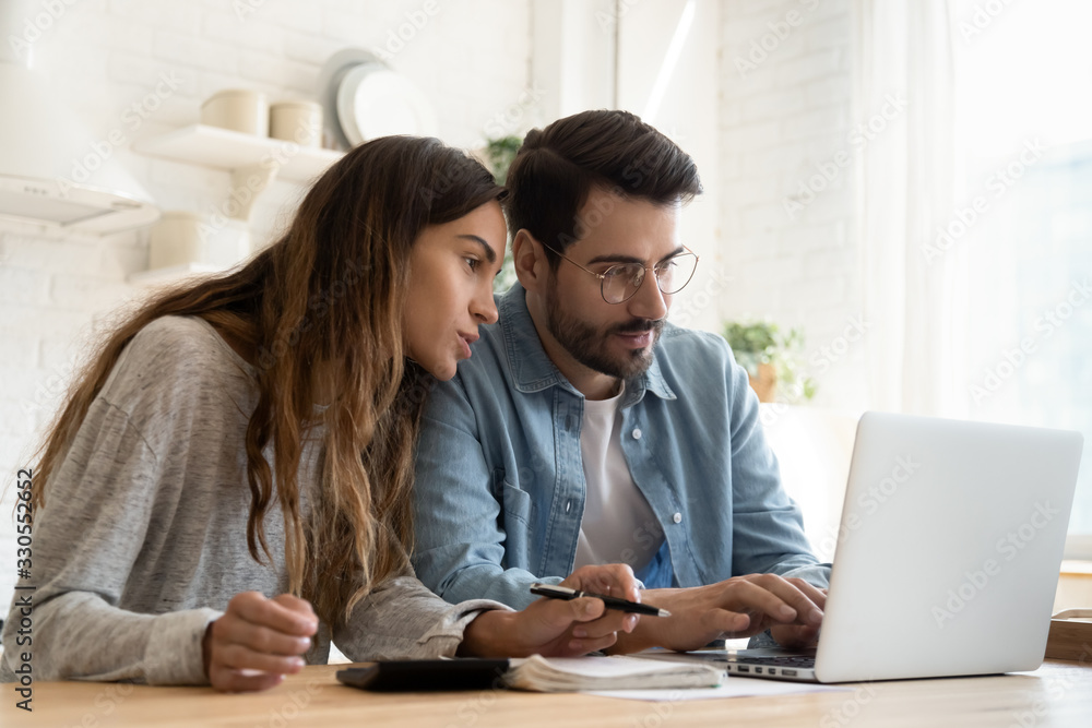 Fototapeta Focused young couple calculating bills, discussing planning budget together, serious wife and husband looking at laptop screen, using online banking services and calculator, checking finances