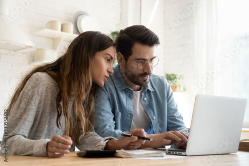 Focused young couple calculating bills, discussing planning budget together, serious wife and husband looking at laptop screen, using online banking services and calculator, checking finances