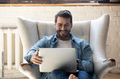 mata magnetyczna Smiling young man wearing glasses using laptop, sitting in cozy armchair, happy male looking at computer screen, chatting in social network or shopping online, playing game, working at home