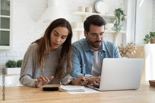 Fototapeta Serious man and woman calculating bills, using calculator and laptop, online banking services, family discussing and planning budget, focused wife and husband checking finances together obraz