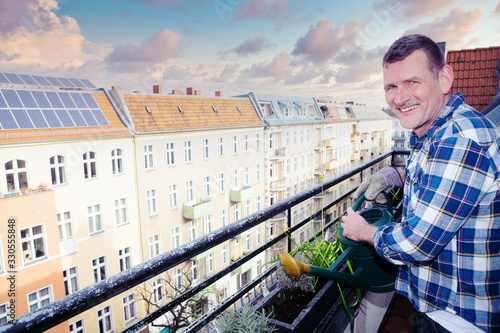 handsome man in his 50s watering plants on balcony Poster Mural XXL