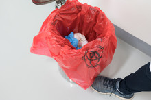 Close Up Scientist Foot And Red Bag With Bioharzard Sign.Worker Foot Pushing Red Garbage Bag.Maid And Infection Waste Bin At The Indoor Public Building.Infectious Control.