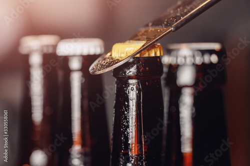 Obraz Row brown ice cold beer bottle with water drops and metal opener cap, dark background - fototapety do salonu