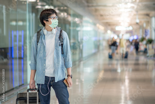 Obraz Asian man wearing face mask walking his suitcase luggage in airport terminal. Coronavirus (COVID-19) outbreak prevention when travel abroad. Health awareness for pandemic protection - fototapety do salonu