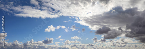 Fotografering Dramatic windblown clouds against a blue sky