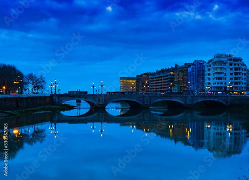 Fototapeta View on Santa Catalina bridge over Urumea river at night in San Sebastian