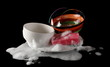 Clean washed dishes, plates and bowl with red sponge and dishwashing liquid with foam isolated on black background