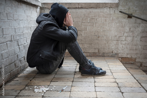 A young drug addict experiencing a drug addiction crisis, sitting in an abandoned house Canvas Print
