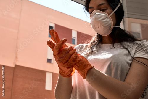 Mujer joven con máscara y guantes para evitar el contagio. Wallpaper Mural