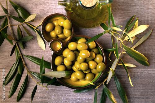 Aceitera con aceite de oliva virgen y aceitunas verdes frescas vista cenital Wallpaper Mural