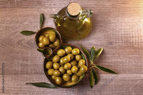 Aceitera con aceite de oliva virgen y aceitunas verdes frescas vista cenital Canvas Print