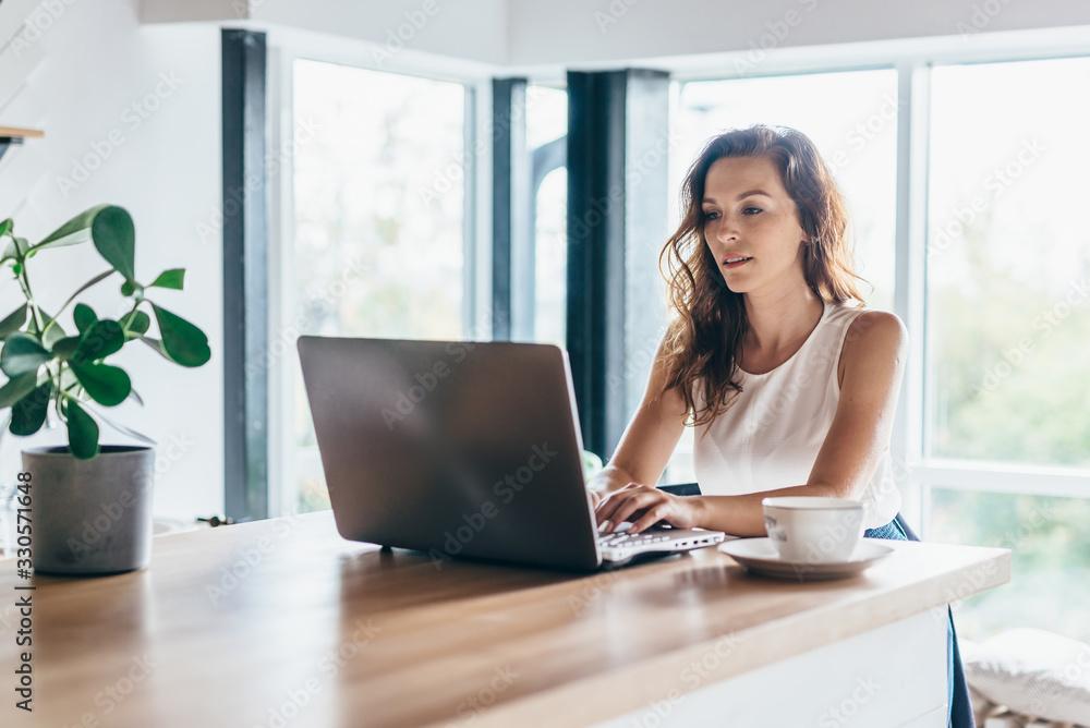 Fototapeta Woman using laptop while sitting at home