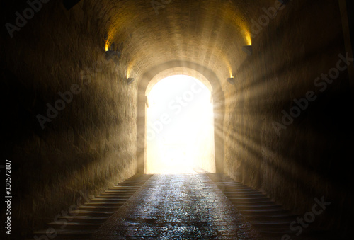 Fotografie, Obraz A bright yellow glowing light breaking through at the end of a dark tunnel