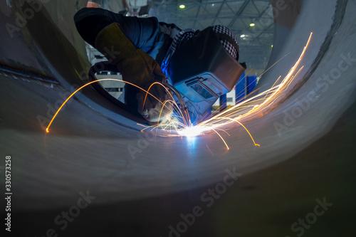 Photo Welder performs welding work semi-automatic electric arc welding