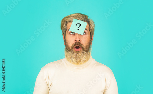 Thinking bearded man with question mark on blue background Canvas Print