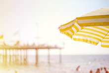 There Is A Large Yellow-white Striped Umbrella On The Beach