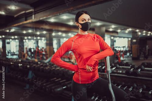 obraz PCV Coronavirus covid-19 prevention, fitness girl with a medical mask holding a dumbbell . Fighting viruses.