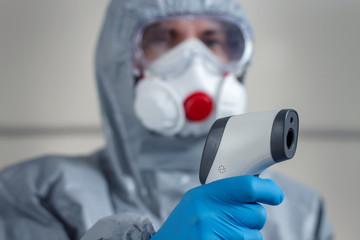 Na pierwszym planie dłoń ubrana w rękawiczkę jednorazową trzyma termometr laserowy i mierzy temperaturę. W tle postać ubrana w kombinezon ochronny, maskę na twarz i okulary ochronne.