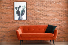 Comfortable Sofa Near Brick Wall