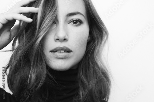 Fotografia Black and white portrait of a young serious woman looking directly in camera