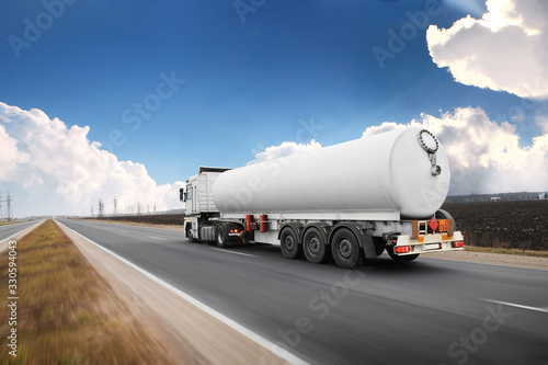Fotografía Big fuel tanker truck shipping fuel on the countryside road in motion against sk