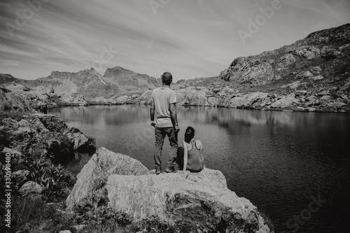 Couple de randonneurs admirant la vue du lac et de la montagne Canvas Print