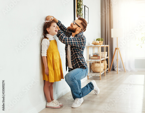 Fotografía father measuring height of daughter at home.